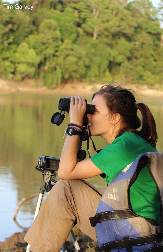 Helen Pople looking through binoculars in the field