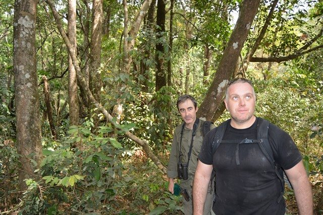 Stuart and Ash hiking through the forest to check camera traps