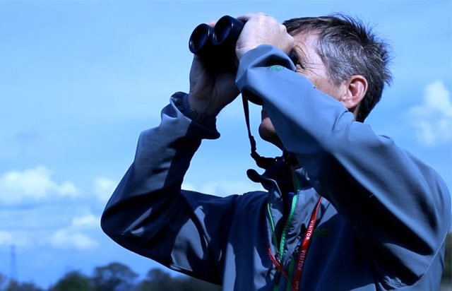 Man with binoculars looking out for birds