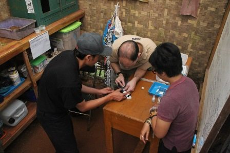 Javier training keeper and veterinary staff in microchipping procedures.